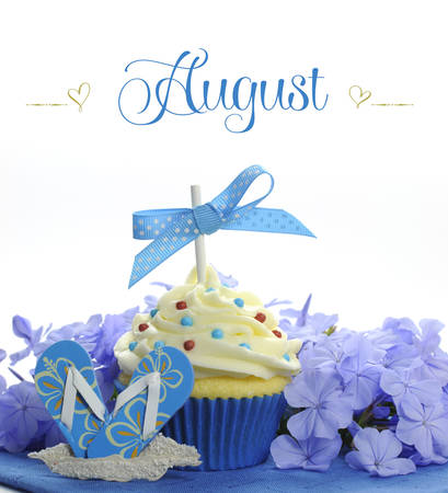 Beautiful blue Summer holiday theme cupcake with seasonal flowers and decorations for the month of August with sample text or copy space for your text here  photo