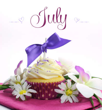 Beautiful purple and pink Summer theme cupcake with seasonal flowers and decorations for the month of August with sample text or copy space for your text here  photo