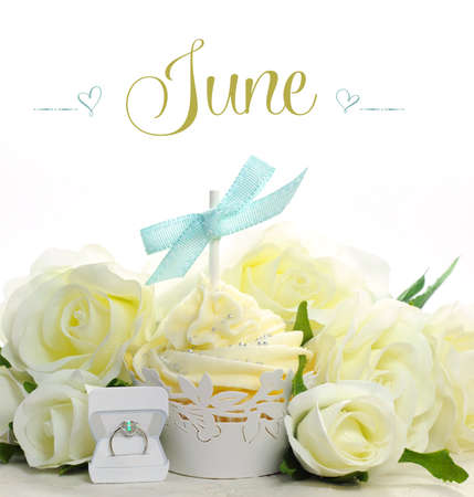 Beautiful white June Bride theme cupcake with seasonal flowers and decorations for the month of June with sample text or copy space for your text here  photo