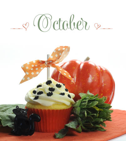 Beautiful orange Halloween theme cupcake with seasonal flowers and decorations for the month of October with sample text or copy space for your text here  photo