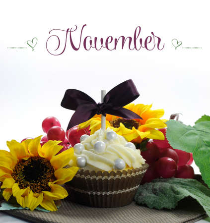 Beautiful Fall Thanksgiving theme cupcake with seasonal flowers and decorations for the month of November with sample text or copy space for your text here  photo