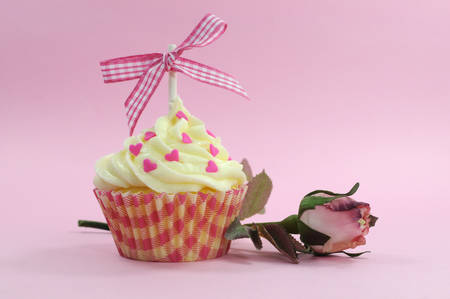 Pretty pink cupcake with pale pink silk rose bud on pink for female birdthay, wedding, Valentine or Mothers Day  photo