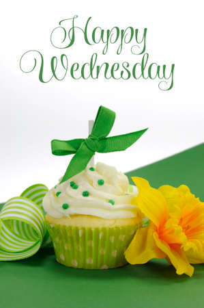 Beautiful green decorated cupcake with daffodil and stripe ribbon on green with Happy Wednesday sample text or copy space for your text here  photo