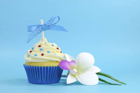 Beautiful blue cupcake with orchid flower on blue , for birthday, wedding, baby shower or special occasion  photo
