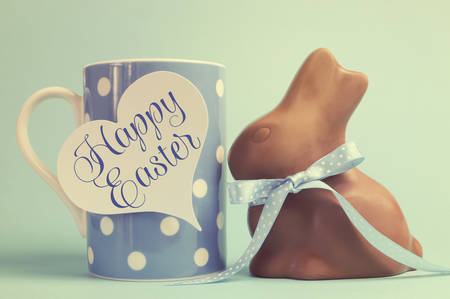 Retro vintage old fashion style Happy Easter chocolate bunny with coffee mug and heart tag on faded blue background. photo
