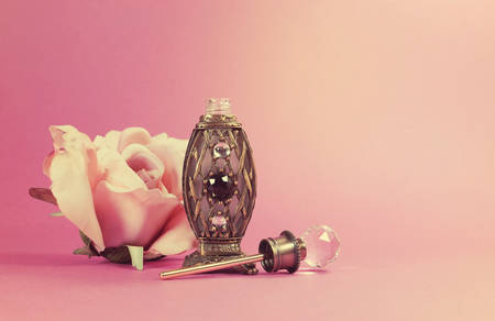Vintage perfume bottle with crystal stopper and silk rose on retro style feminine pink background with copy space for your text here.