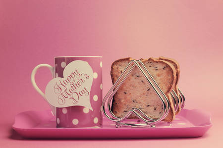 Retro vintage old fashion style Happy Mothers Day breakfast with toast and polka dot coffee tea cup and heart shape rack on faded pink background.