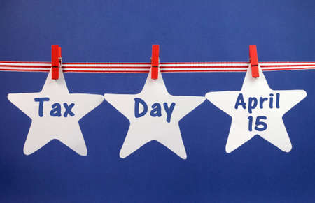 Tax Day April 15, for USA tax day reminder, greeting or message across white stars hanging from pegs on a line against a blue background.
