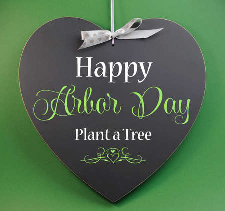 Happy Arbor Day, Plant a Tree, greeting message sign on heart shaped blackboard against a green background.