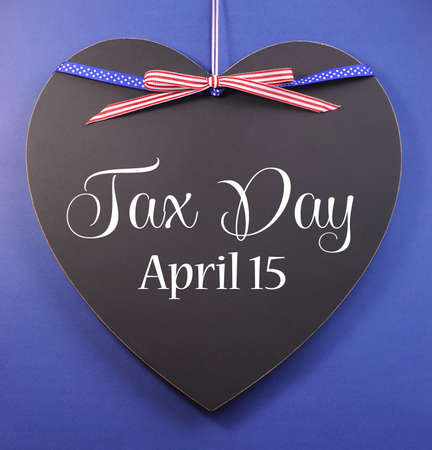 Tax Day, April 15, reminder greeting message with USA ribbon on a heart shaped blackboard against a blue background. Stock Photo