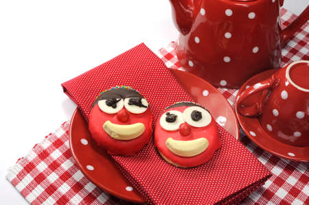 Fun cute childrens handmade cookie with candy face and red polka dot cup of tea or coffee for Mothers Day, birthday or Fathers day with sample text or copy space  photo