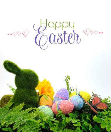 easter egg hunt: Happy Easter scene with moss bunny and colorful glitter eggs, daffodil and butterfly on ferns with sample text or copy space for your text here  Stock Photo