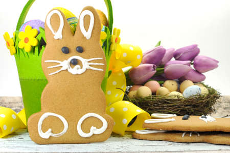 Happy Easter yellow and lime green theme gingerbread bunny cookie with basket, tulips, and candy birds eggs in nest on shabby chic wood and white background  photo