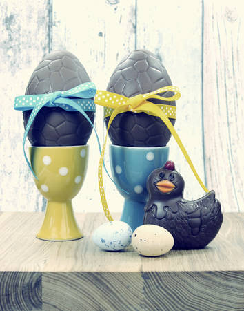 Retro vintage style Happy Easter chocolate eggs in polka dot egg cups with chick and birds eggs on shabby chic wood table background  photo