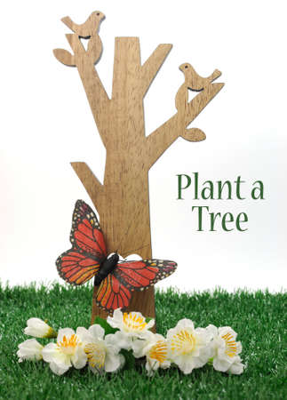 Happy Arbor Day, Plant a Tree greeting for last Friday in April, with wood tree, carved birds, butterfly and green grass on white background with sample text or copy space. photo