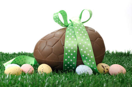 Beautiful Happy Easter large chocolate Easter egg and small candy speckled eggs on grass with white background.
