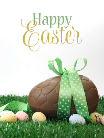 Beautiful Happy Easter large chocolate Easter egg and small candy speckled eggs on grass with sample text or copy space for your text here.