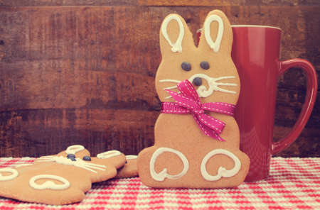 Retro vintage style Happy Easter bunny rabbit gingerbread cookies with coffee mug on red check table with dark wood recycled timber background. photo