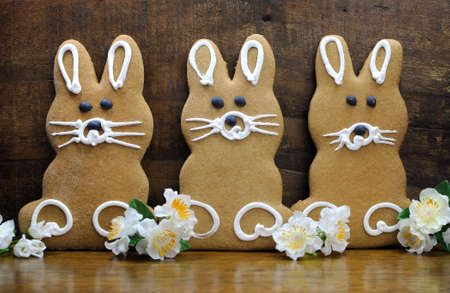 Group of three Happy Easter bunny rabbit gingerbread cookies on rustic country style natural wood recycled timber background photo
