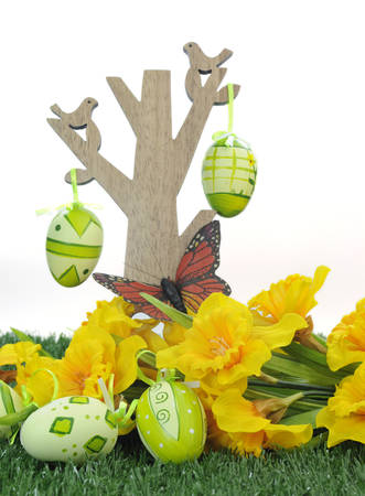 Happy Easter tree with butterfly and colorful pink and green Easter Eggs with yellow daffodils on green grass against white background  photo