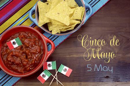 mesa de la fiesta de celebración con chips de maíz y salsa dip, banderas mexicanas con Feliz Cinco de Mayo, 5 de mayo de texto