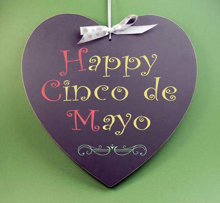 mayo: Happy Cinco de Mayo handwriting greeting on heart shaped blackboard on green background  Stock Photo