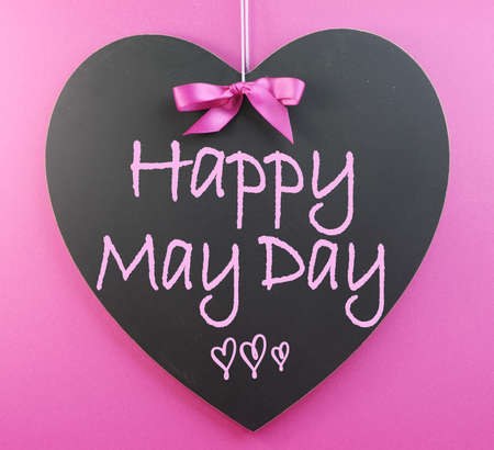 Happy May Day handwriting greeting on heart shaped blackboard on pink background  Stock Photo