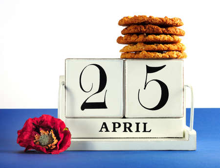 tucker: White shabby chic vintage style block calendar for Anzac Day, April 25, with traditional Anzac biscuits on white background with remembrance red poppy Stock Photo