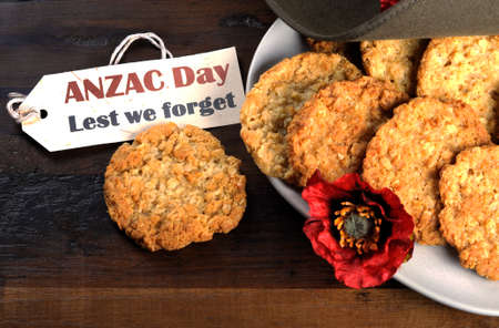 Australian army slouch hat and traditional Anzac biscuits on dark recycled wood with remembrance red poppy with Anzac Day, Lest We Forget tag.