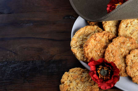 Australian army slouch hat and traditional Anzac biscuits on dark recycled wood photo
