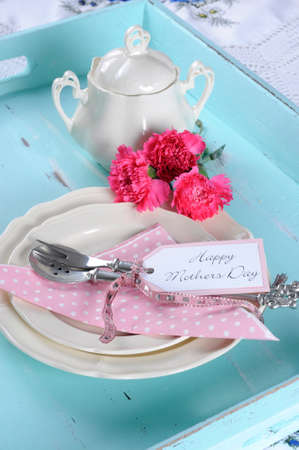 Happy Mothers Day aqua blue breakfast morning tea vintage retro shabby chic tray setting with antique fine china plates, pink carnations and sugar bowl. photo