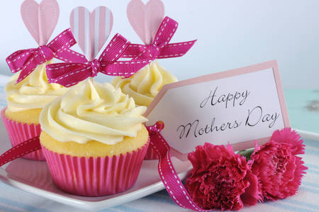 Happy Mothers Day aqua blue vintage retro shabby chic tray with pink cupcakes close up with pink hearts and ribbon decoration and gift tag Stock Photo