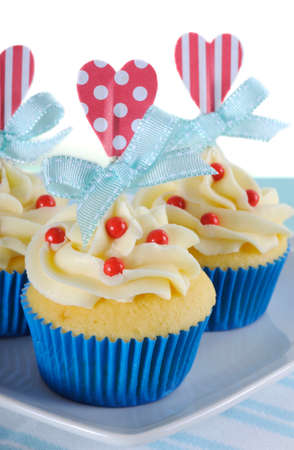 Happy Fathers Day bright and cheery red white and blue decorated cupcakes with heart toppers and gift tag on vintage blue shabby chic background. photo