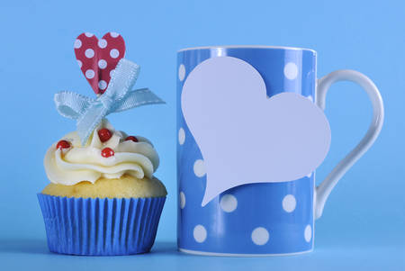 Fancy blue theme cupcake with red and white decorations with heart topper and polka dot coffee mug for birthday or special occasion gift on pale blue background. photo