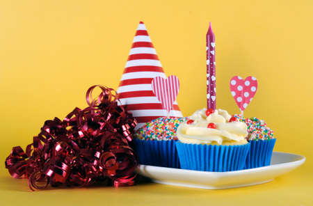 occasion: Bright and cheery red blue and yellow theme cupcakes with hundred and thousands candy topping and heart toppes for birthday or special occasion on yellow background