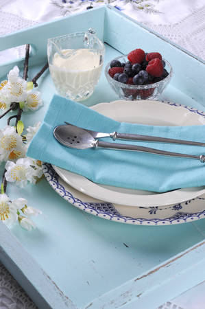 Beautiful vintage retro style aqua dessert tray setting with antique fine china serving table setting with red berries, raspberries and blackberries, and cream  photo