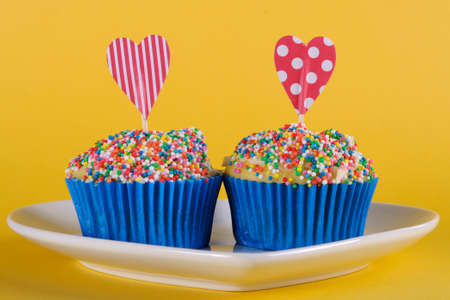 Bright and cheery red blue and yellow theme cupcakes with hundred and thousands candy topping and heart toppes for birthday or special occasion on yellow background  photo