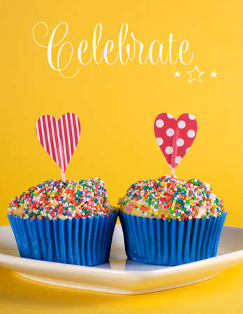 Bright and cheery red blue and yellow theme cupcakes with hundred and thousands candy topping and heart toppes for birthday or special occasion with sample Celebrate text or copys space   photo