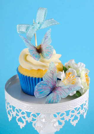 Beautiful blue butterfly theme cupcake on white cupcake stand with greeting gift tag against a blue background  Close up  photo