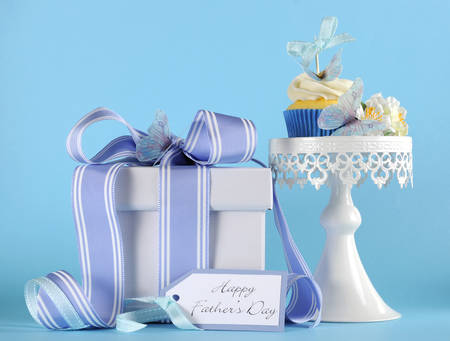 Happy Fathers Day blue butterfly theme cupcake on white cupcake stand with gift and greeting gift tag against a blue background  photo