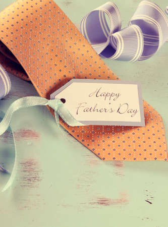 cele: Retro style Happy Fathers Day yellow tie with gift tag on vintage aqua blue rustic shabby chic table - vertical with copy space. Stock Photo