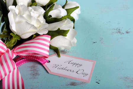 Happy Mothers Day gift of white roses bouquet with pink stripe ribbon and gift tag with greeting on aqua blue vintage shabby chic table. Stock Photo