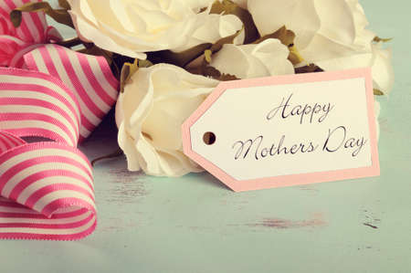 mothers day: Retro style Happy Mothers Day gift of white roses bouquet with pink stripe ribbon and gift tag with greeting on aqua blue vintage shabby chic table.