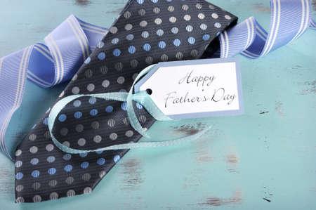 lazo regalo: Día de padres feliz corbata azul con etiqueta de regalo en la aguamarina azul rústica mesa elegante lamentable de la vendimia con el saludo y la cinta azul de la raya.