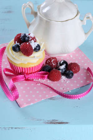 Delicious cupcake with berries and vintage sugar bowl on retro aqua blue shabby chic table, with copy space for your text here. photo