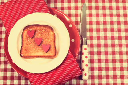 Retro vintage style red check table setting with polka dot plate and knife and toast with hearts for Mothers Day, romantic or Valentine breakfast. photo