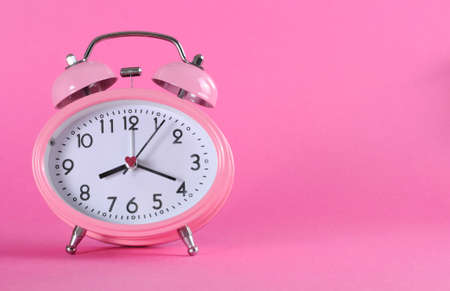 Pretty pink vintage retro style alarm clock with copy space on pink background for daylight saving, time keeping, or baby girl nursery. photo