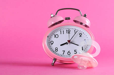 Pretty pink vintage retro style alarm clock with baby dummy pacificer on pink background for baby girl nursery. photo