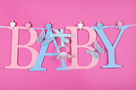 Baby nursery pink and blue letters bunting with dummy pacifier hanging from pegs on a line against a pink background baby shower or newborn girl greeting card. Imagens