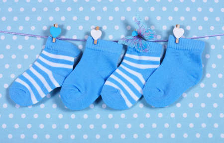 its: Baby boy nursery blue socks and butterfly hanging from pegs on a line against a blue polka dot background for baby shower or newborn greeting card  Stock Photo